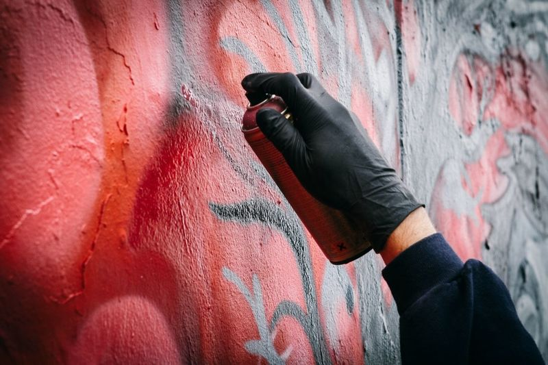 Close-up of persons hand tagging wall with graffiti