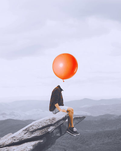 Digital Composite Image Of Decapitated Man With Balloon Sitting On Rock Against Sky