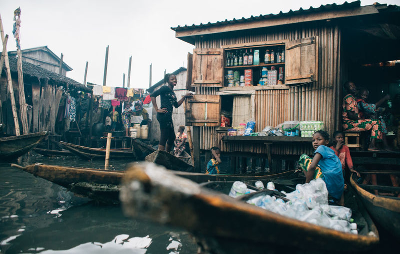 Makoko Slum Architecture Building Building Exterior Built Structure Canal Day Group Of People Men Nature Nautical Vessel Occupation Outdoors People Real People Selective Focus Standing Transportation Water Women