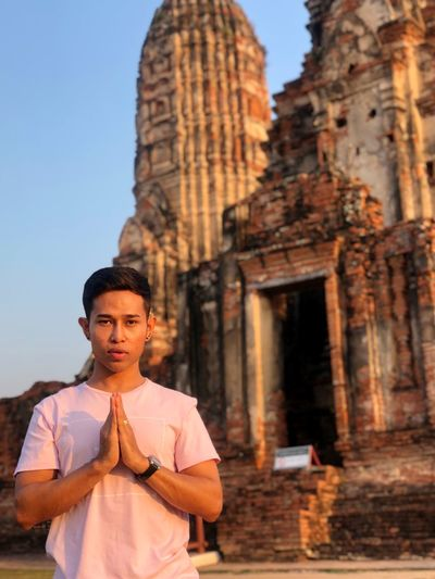 Portrait Of Young Man In Prayer Position Standing Against Temple