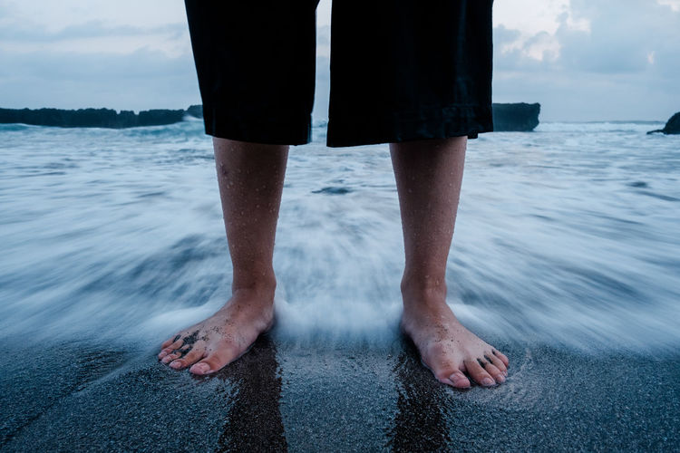 A woman stands at a beach, next to the crushing waves. Motion Blur Wave Adult barefoot Beach Body Part Day Human Body Part Human Foot Human Leg Land Lifestyles Low Section Motion Nature One Person Real People Sea Standing Water Waves Wet