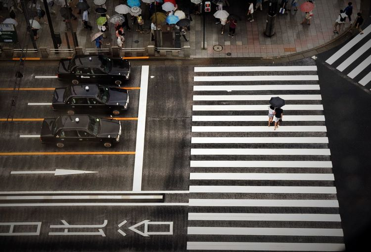 High Angle View Of People Holding Umbrella While Walking On City Street