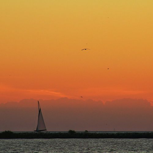 Sailboat Against Orange Sky At Dusk