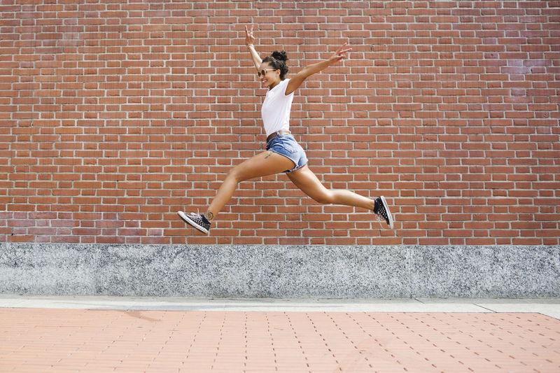 Full length of woman jumping against brick wall