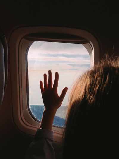 Rear view of girl looking through window while traveling in airplane