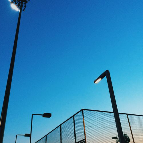 Low angle view of street lights by chainlink fence against clear sky