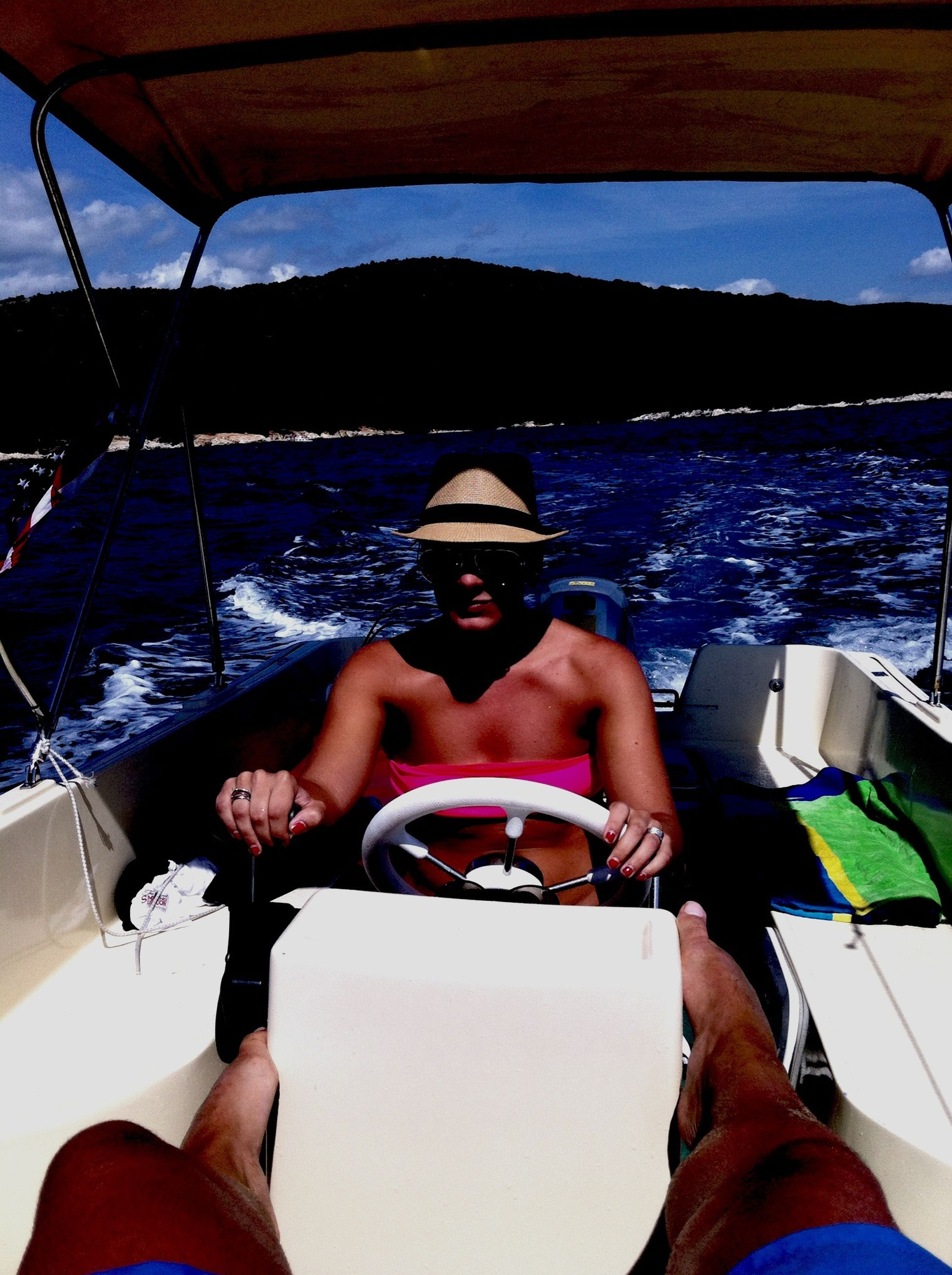 lifestyles, leisure activity, transportation, mode of transport, water, sitting, nautical vessel, sea, vehicle interior, boat, sunglasses, travel, part of, young adult, relaxation, men, vacations, personal perspective