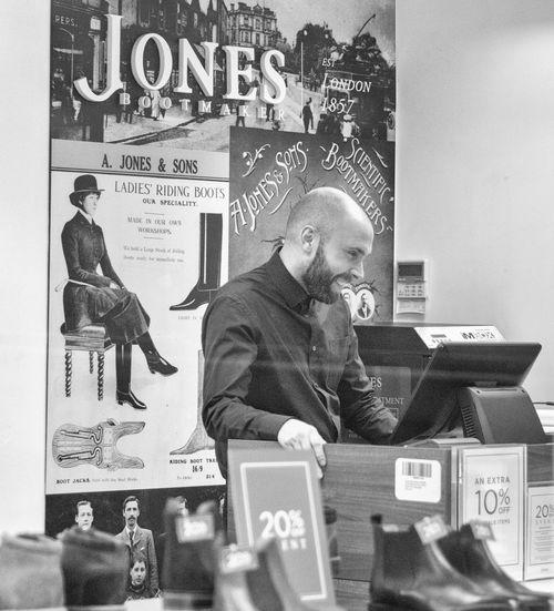 Black and white Street Photography in Bury St Edmunds Black And White Street Photography Boots Jones Bald Head Beard Bearded Bearded Man Black And White Black And White Collection  black and white friday Black And White Photography Bootmaker Portrait Retail  Retail Store Shop Shop Assistant Shop Front Store Street Street Photography Streetphoto_bw Streetphotography Till