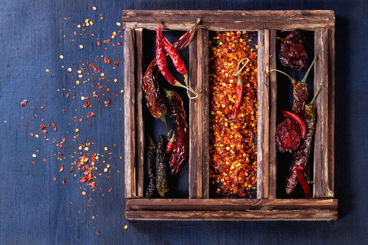 High angle view of dried red chili peppers in wooden box on table