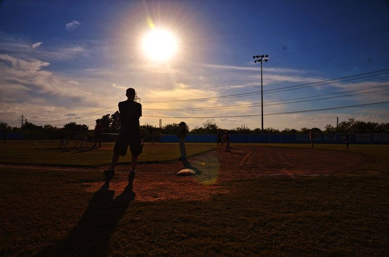 Silhouette players playing baseball on field against sky during sunset