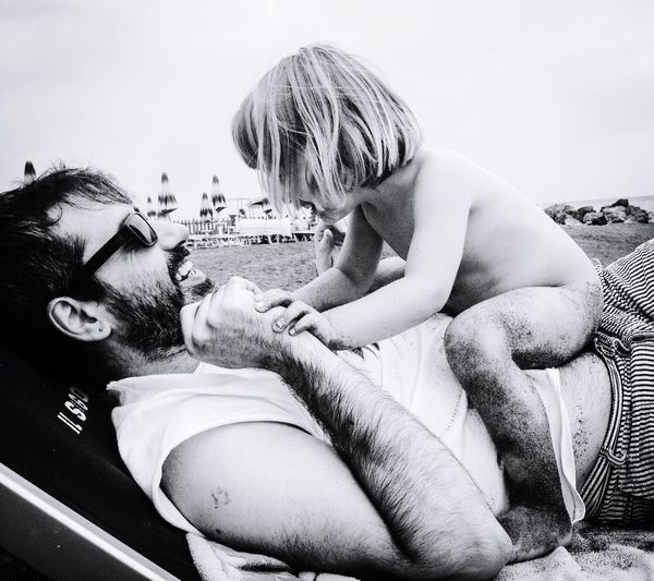 Cute girl playing with father at beach