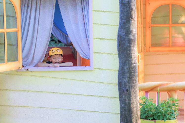 Portrait of boy in front of window