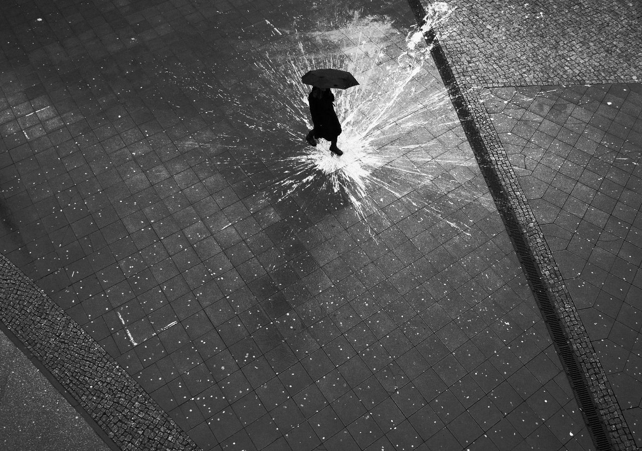 High angle view of silhouette man walking on wet street during rainy season