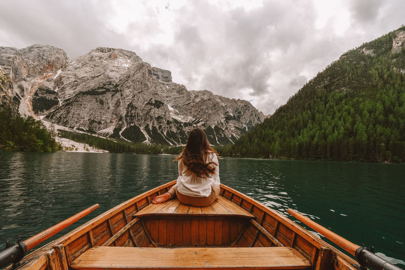 Woman in boat on lake against mountains