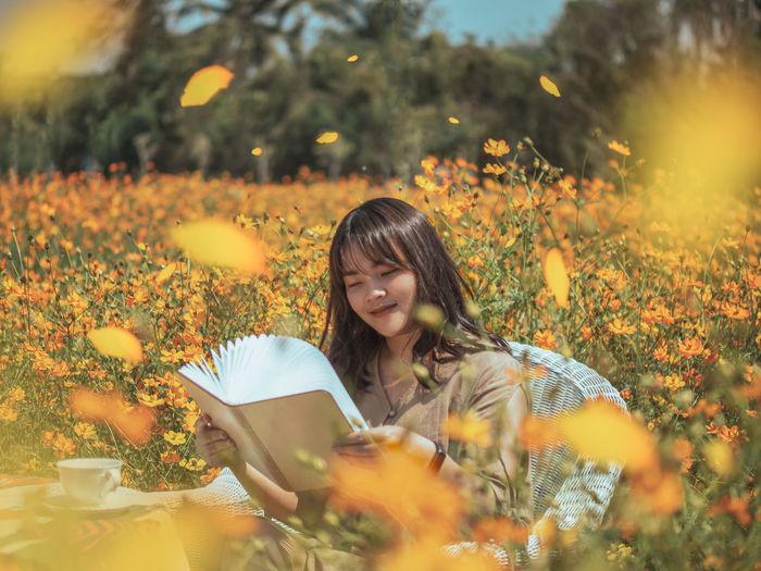 Portrait of woman holding flowers on field