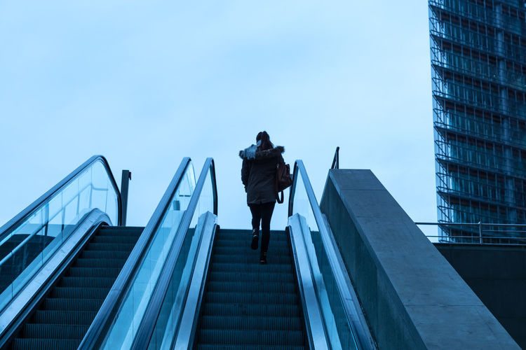 Low angle view of woman moving up on escalator against sky