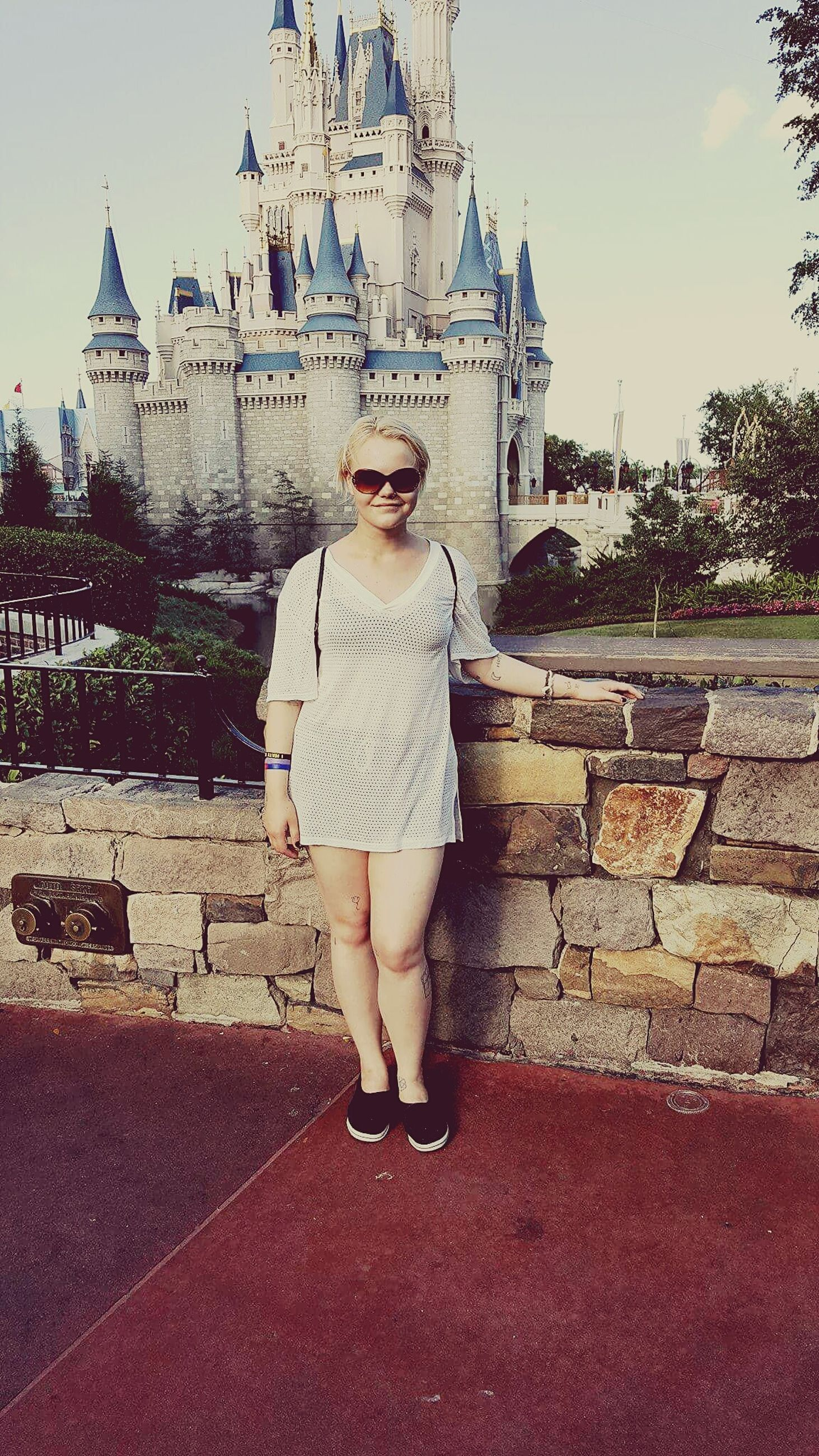 real people, architecture, building exterior, built structure, front view, young women, young adult, full length, one person, sunglasses, lifestyles, leisure activity, outdoors, looking at camera, casual clothing, day, standing, portrait, beautiful woman, travel destinations, smiling, retaining wall, sky