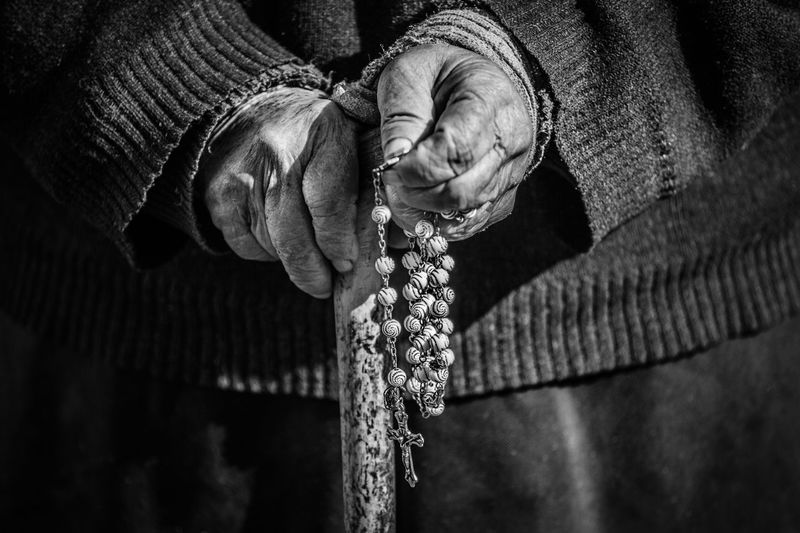 Close-Up Of Midsection Woman Holding Rosary Beads