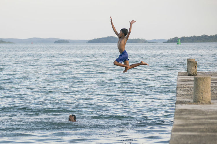 Full Length Mid-air Jumping Vitality Fun Excitement Motion Exhilaration Freedom Happiness Skill  Swimming Arms Raised Day Water Outdoors Cheerful Sea Adventure Nature Beauty In Nature Seascape Check This Out Childhood Swim Carnival Crowds And Details Flying High Art Is Everywhere Live For The Story