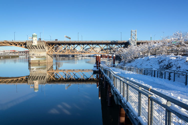 PORTLAND, OR - JANUARY 12: Eastbank Esplanade in Portland, OR with the Moda Center in the background on January 12, 2017 Architecture Center City Downtown Ice Oregon Pacific Portland Portland, OR Tree Trees USA Winter Burnside  Cold Colorful Icy Northwest Old River Snow Town Urban Waterfront White