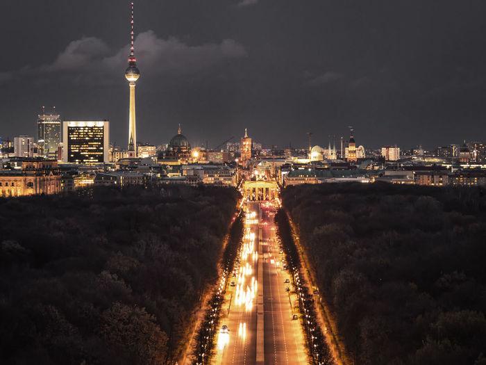 Illuminated Road Leading Towards City Against Sky