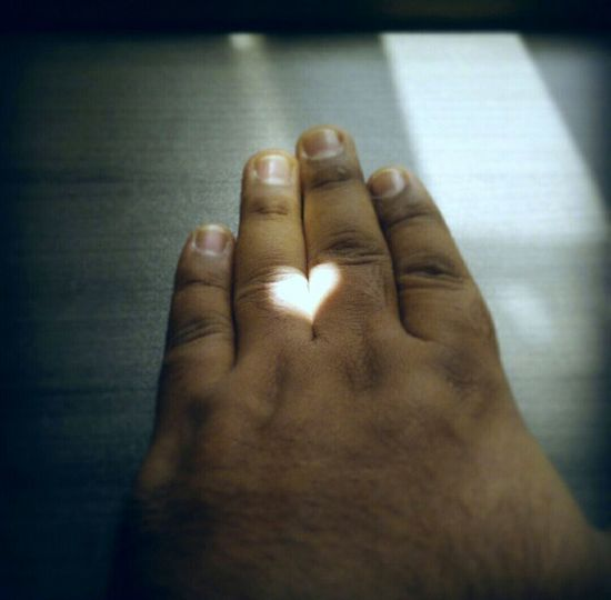 High angle view of sunlight forming heart shape on hand
