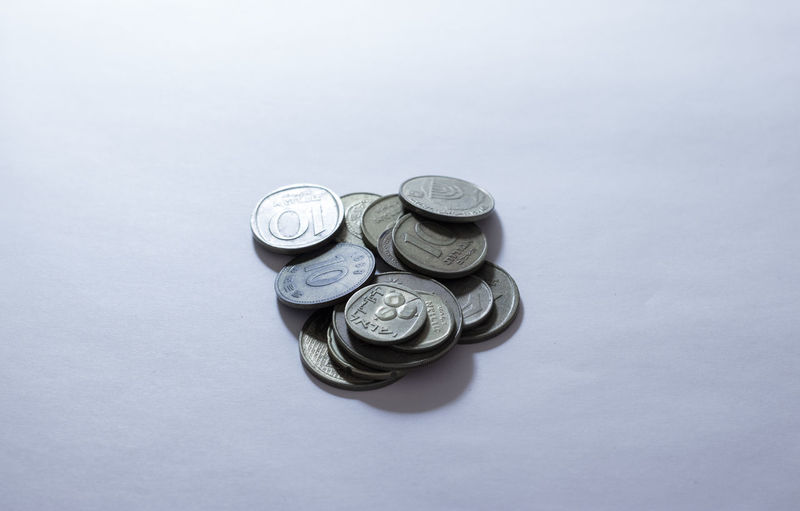 High angle view of coins on white background
