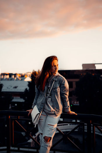Young woman looking away against sky during sunset