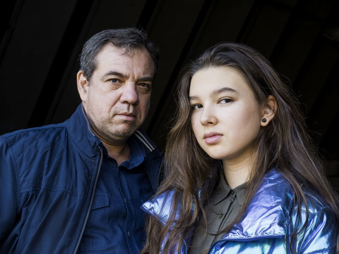 Portrait of mature man with daughter against black background