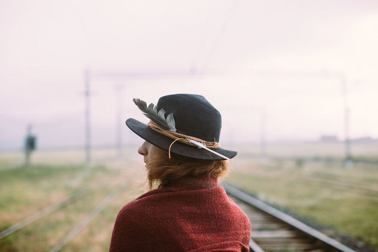 Rear view of woman wearing hat standing on railroad track against sky