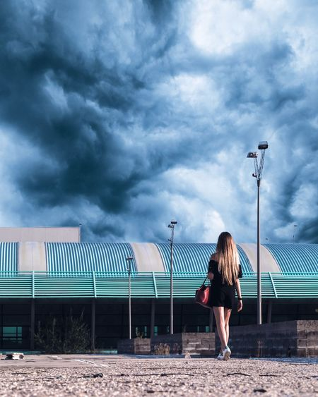 Rear view of woman walking on street against cloudy sky