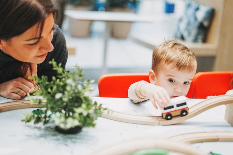 Baby boy by mother playing with toy car