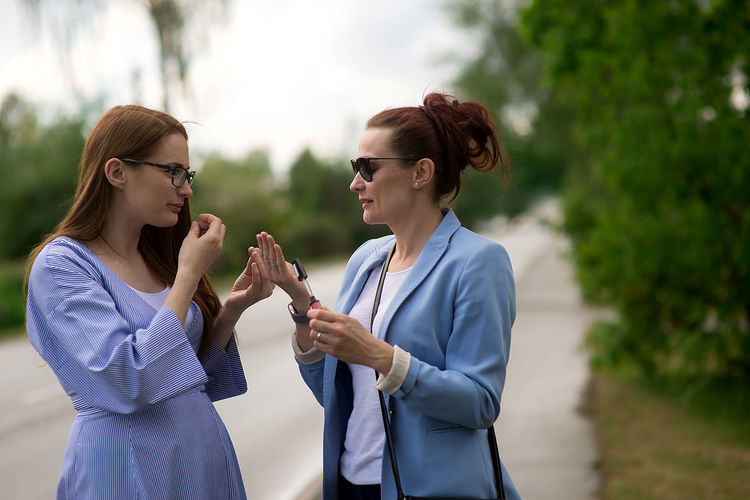 Two young women sisters talking and painting her lips with lipstick on the street