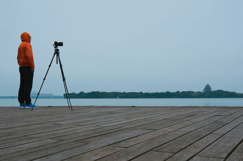 Photographer with city skyline China Water Photography Themes Real People One Person Tripod Camera - Photographic Equipment Photographic Equipment Rear View Sky Lake Standing Photographing Day Lifestyles Photographer Outdoors Digital Camera