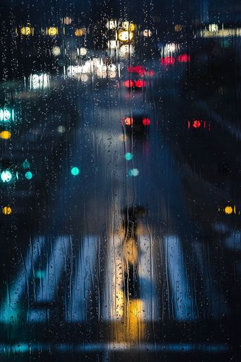 Road seen through wet window during rainy season