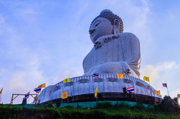 Amazing Massive white marble Buddha statue, the famous tourist attraction on top of hill in Phuket, Thailand. Big Buddha Marble Statue Massive Stone Buddha Beauty In Nature Big Buddha Temple Big Buddha Statue Big Buddha, Thailand Day Flag Giant Buddha Low Angle View Marble Buddha Marble Stone Nature No People Outdoors Patriotism Sculpture Sky Statue Worship Places