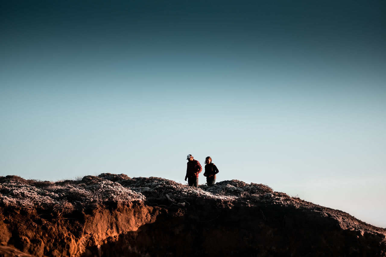 Low angle view of people standing on mountain against sky