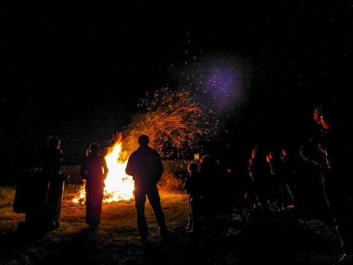People standing by bonfire at night