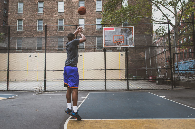 Young man practicing basketball in court