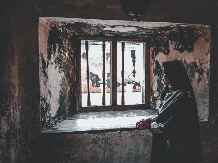 Rear view of man standing against window in abandoned building