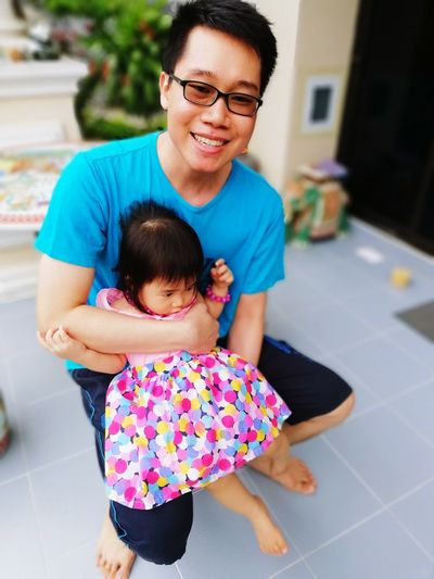 High Angle View Of Father Holding Cute Daughter While Sitting Outdoors