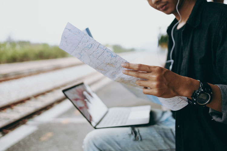 Midsection of man holding paper