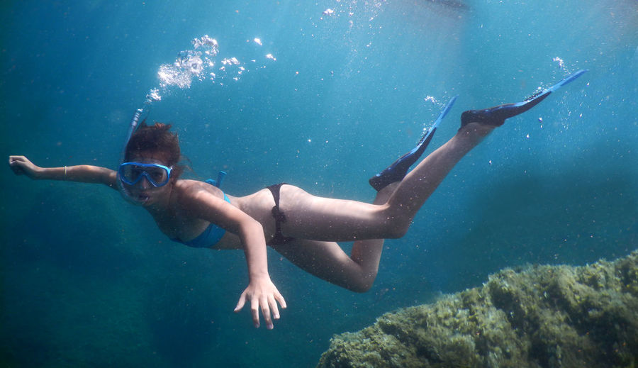Young woman in bikini snorkeling undersea