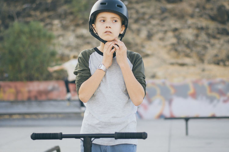 Boy wearing helmet while standing outdoors