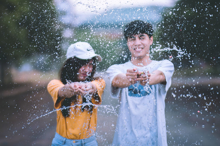 Portrait of smiling couple splashing water on road