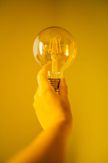 Person holding light bulb against yellow background