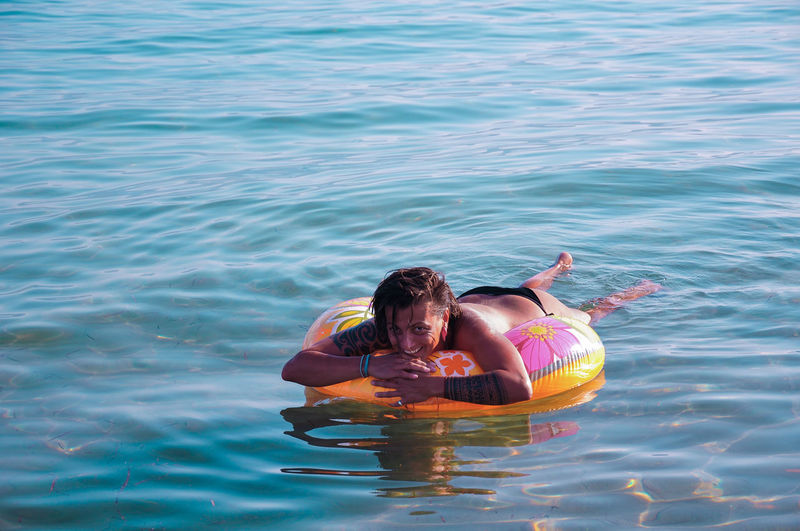 Portrait of mid adult woman with inflatable ring floating on sea