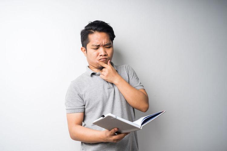 Man holding mobile phone against white background