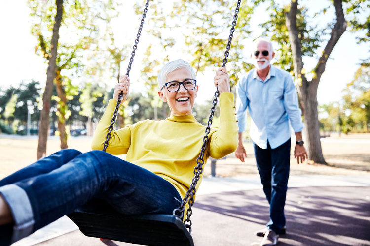 Happy woman playing on swing against man looking at her