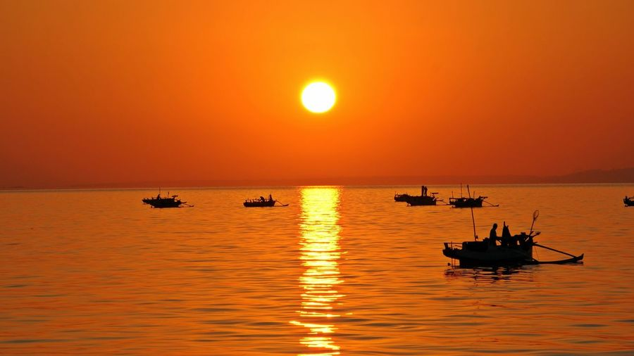Silhouette boats on sea against sky